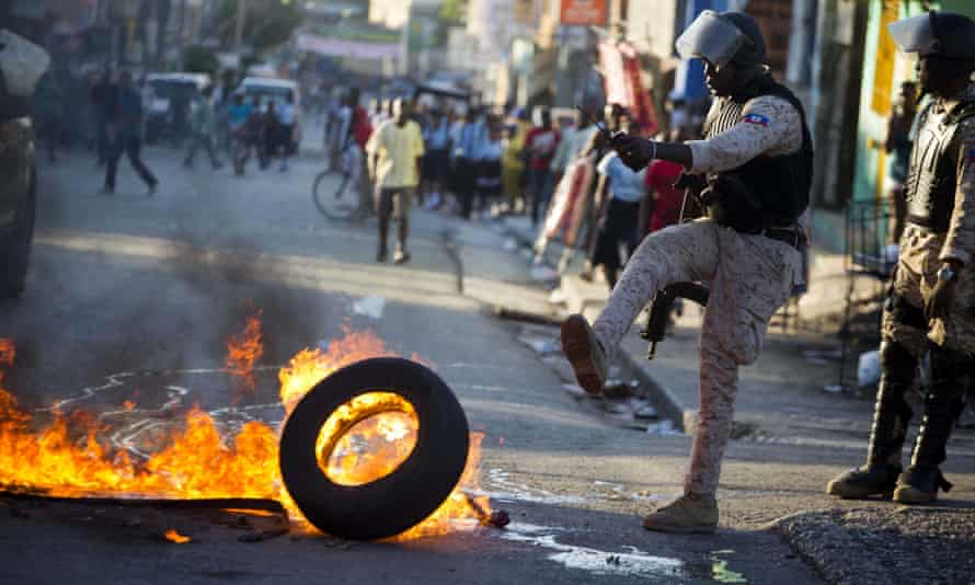 A police officer removes a tire set fire by supporters of presidential candidate Maryse Narcisse.