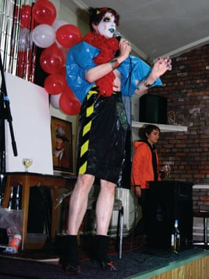 """David Hoyle & Jayne Compton 'Keep it in the Family', The Carlton Club September 2010  """"Here we see Jayne and David in their natural habitat – a peculiar social club in the Whalley Range area of Manchester. Note David's Haçienda-style skirt seam. I've been following David's career since the mid 1990s and he's always had a cracking pair of legs.""""  Jayne Compton of Switchflicker Productions. Jayne has been responsible for many pioneering ventures including award-winning theatre productions, club nights and a record label. Jayne and David are an incendiary team. They make unforgettable stuff happen."""""""