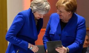 Theresa May and Angela Merkel in royal blue jackets looking at an iPad