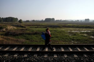 A Syrian girl called Zena is carried by a fellow refugee on the railway tracks in the village of Pythio.