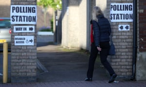 A woman enters a polling station in London.