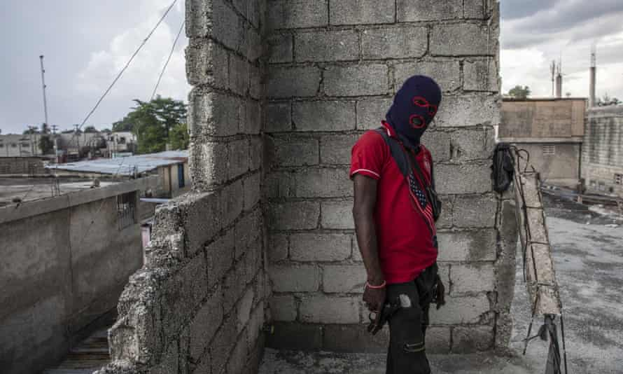 A gang member, wearing a balaclava and holding a gun, poses for a photo in the Portail Léogâne neighborhood of Port-au-Prince.