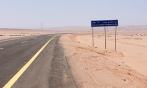 A road sign by a desert highway indicates the distance to the bay at Ras Hameed, Saudi Arabia