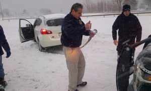 New York Governor Andrew Cuomo helps tow a stranded motorist.