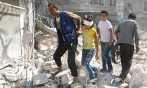 Injured Syrians walk through rubble