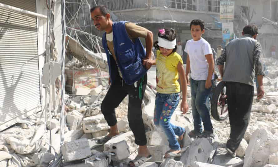 Injured Syrians walk through rubble