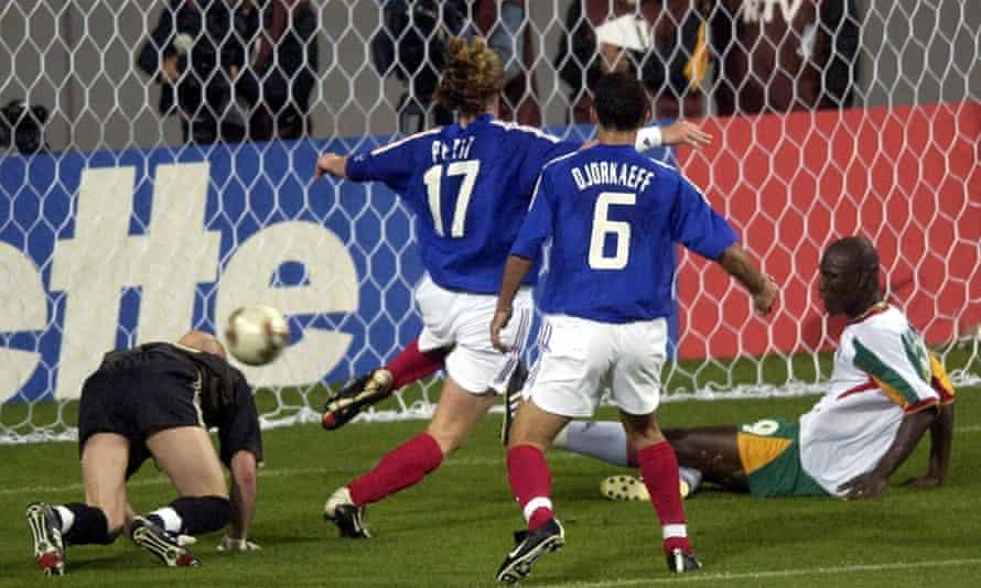Senegal's Papa Bouba Diop pushes the ball past France's goalkeeper Fabian Barthez as Youri Djorkaeff and Emmanuel Petit arrive too late