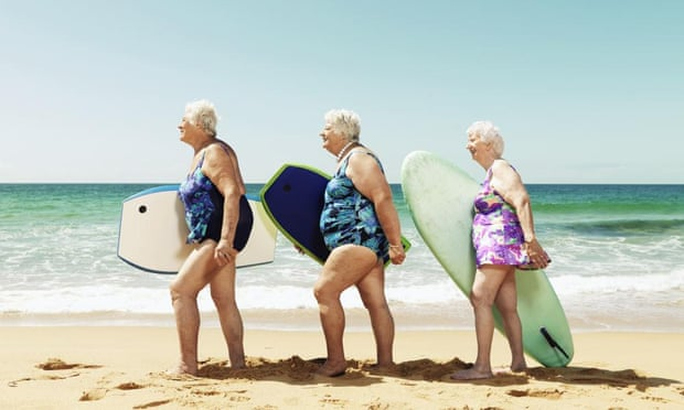 Three women on beach with surfboards in Australia.