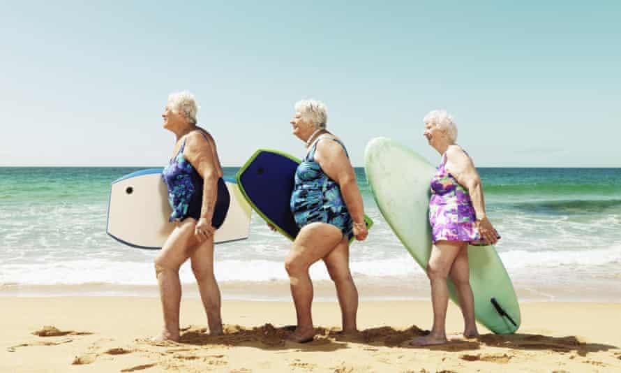 Three women on beach with surfboards in Australia.