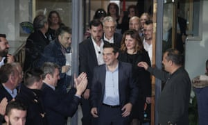 Alexis Tsipras, leader of Greece's Syriza left-wing party, followed by his partner Peristera (Betty) Baziana, greets his supporters outside Syriza's headquarters in Athens, Sunday, Jan. 25, 2015.