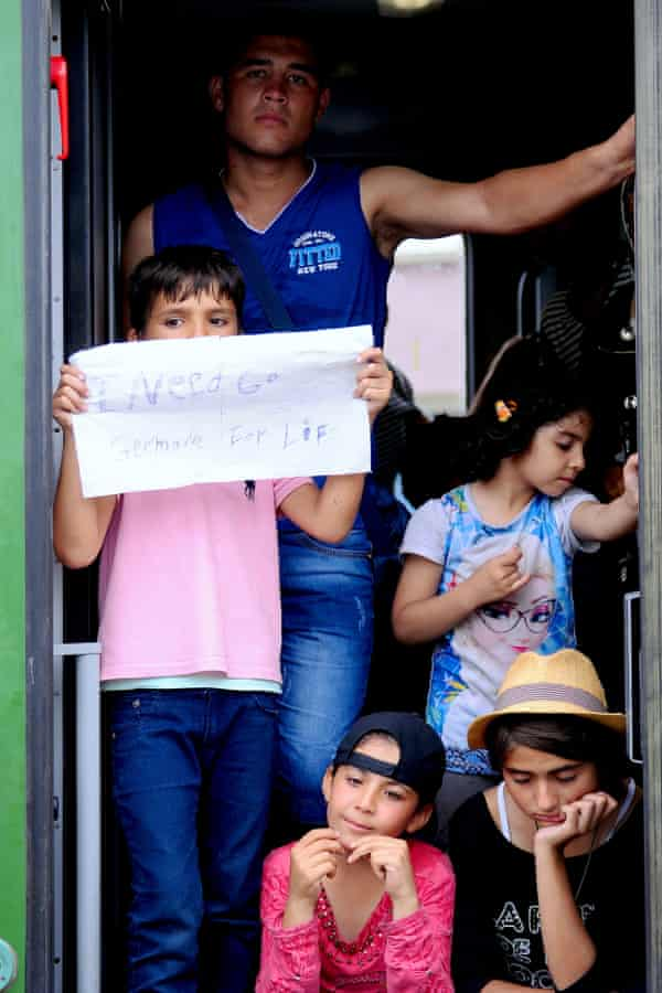 """A young boy holds up a makeshift sign saying """"I need go Germany for life"""" at the door of the train in Bicske."""