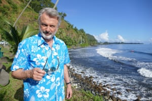 Sam Neill stands in front of a rocky tropical shoreline