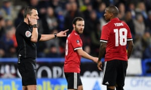 Kevin Friend consults with the Video Assistant Referee as Manchester United players await a decision over a Juan Mata goal.