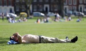 A man sunbathes on Richmond Green in Richmond, Surrey.
