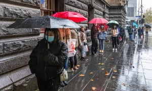 queue of people in winter jackets standing in the rain