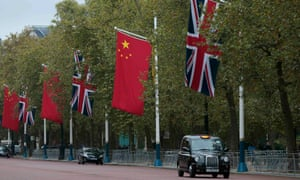 A taxi drives past Chinese and British flags on the Mall in London.
