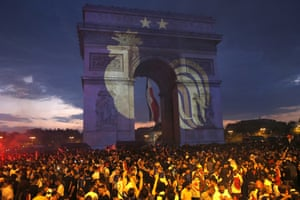 A rooster, a symbol of France, and two stars to indicate two World Cup wins, are projected on to the Arc de Triomphe