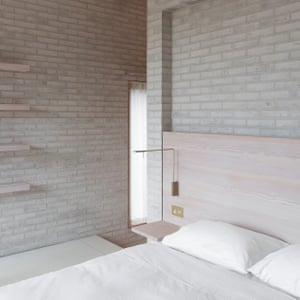 One of the bedrooms, with white sheets against a pale brickwork background at Tŷ Bywyd (Life House).
