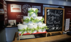 "A picture shows rolls of toilet paper and a sign reading ""1 roll given for every chocolate purchase"" in the Laurent Gerbaudshop in Brussels on 9 April 2020."