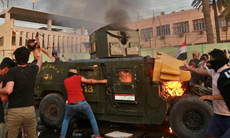 Anti-government protesters burning an armoured vehicle in Baghdad on Thursday.