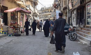 People walk along an alley in the northern Syrian flashpoint city of Manbij.