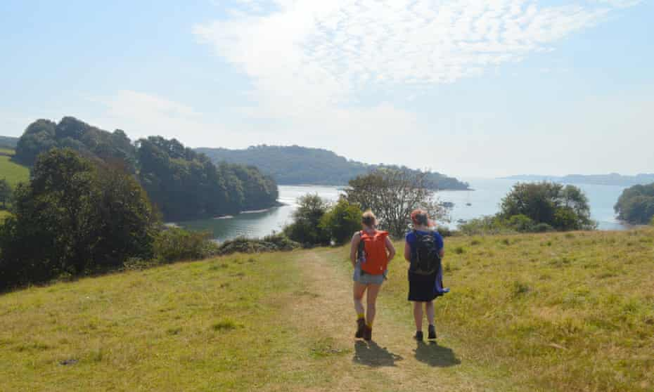 Two hikers in the countryside walk towards the water at Trelissick, Cornwall.