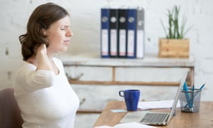 Young stressed businesswoman sitting in front of laptop and holding her neck with pained expression.