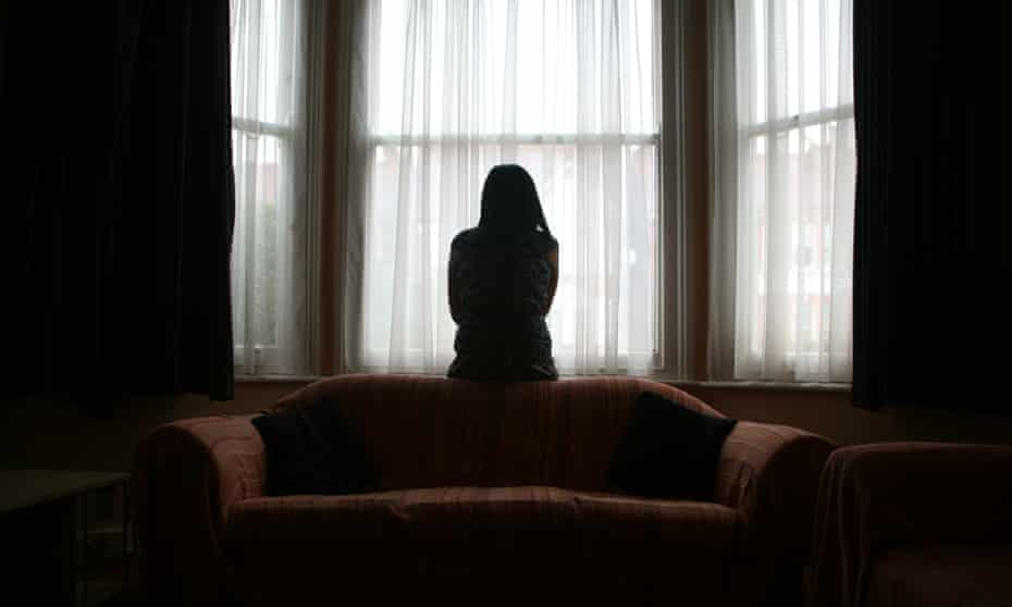 A young Asian woman experiencing domestic violence stands alone in the bay window of her home