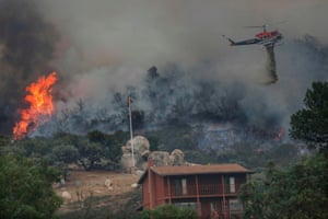 A wildfire encroaches as a helicopter drops water in Jamul. The fire in the Japatul Valley burned 1,619 hectares (4,000 acres) overnight with no containment and 10 structures destroyed