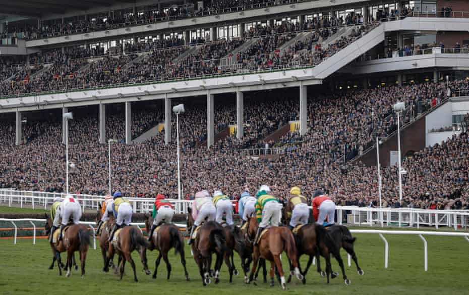 Runners in the opening race pass by the packed main stand during day four of the Cheltenham National Hunt Racing Festival at Cheltenham Racecourse on March 13th 2020 in Gloucestershire