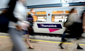 Commuters passing a Govia Thameslink train