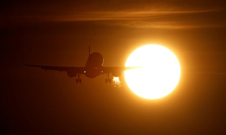 A plane is seen in front of the sun