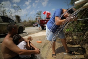 Ciales, Puerto RicoA local resident washes her hair with water from a pipe on the side of a road following the devastation caused by Hurricane Maria