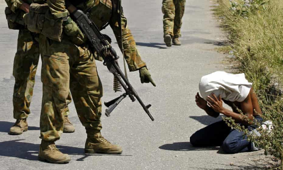 Australian peacekeeping troops detain a man in Dili in 2006