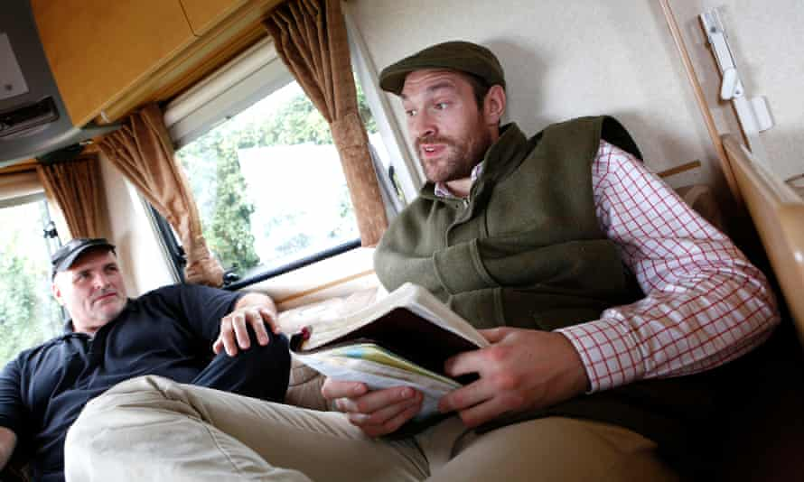 Tyson Fury, with his father, John, reads from the Bible in a caravan at his home near Ormskirk, Lancashire.
