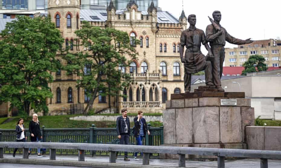 People walk past Soviet era statues the Lithuanian capital, Vilnius