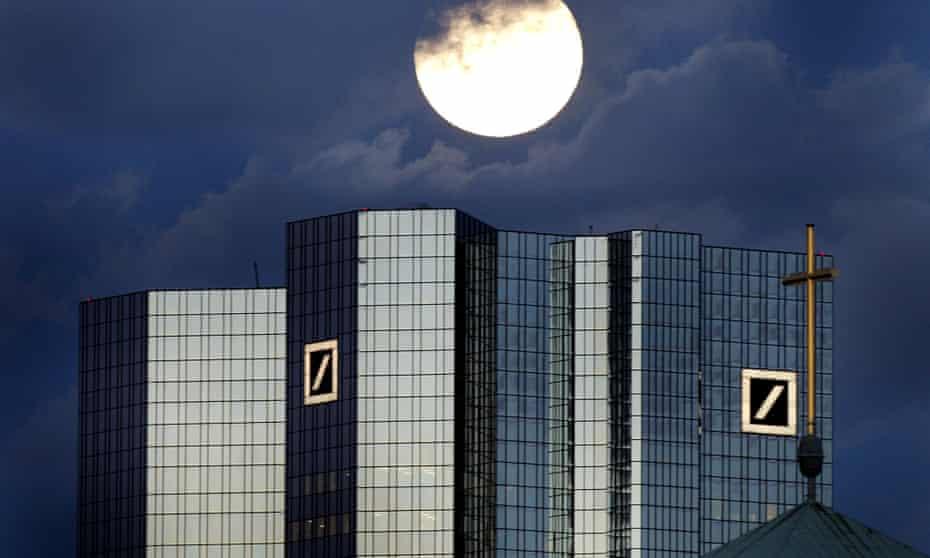 A rising full moon is seen over Deutsche Bank headquarters in Frankfurt.