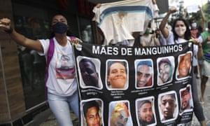 Матери, которые заявили, что их сыновья были убиты во время полицейских операций, держат баннер с фотографиями своих сыновей, во время протеста против преступлений, совершенных полицией против чернокожих людей в фавелах, Рио-де-Жанейро, Бразилия, воскресенье, 31 мая 2020 года.
