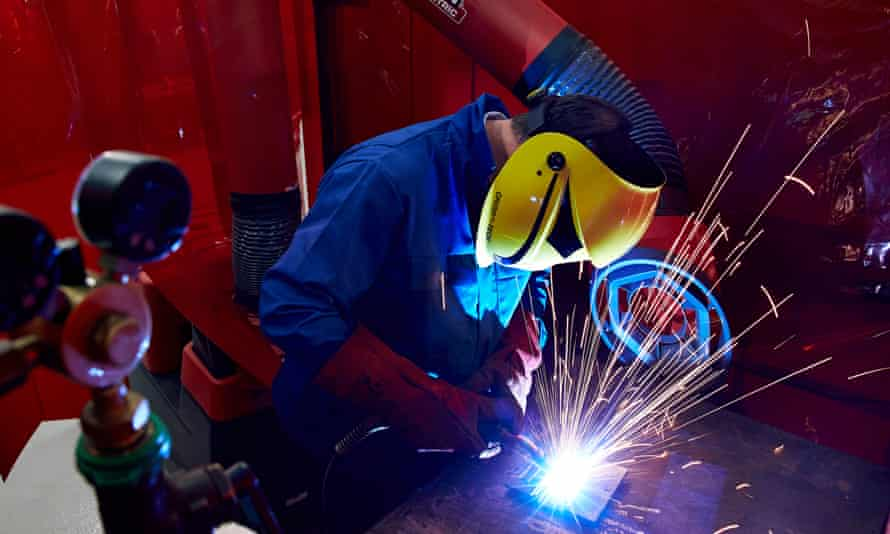 Sparks fly as a skilled worker or welder works with metal in a UK manufacturing factory.