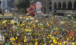 Demonstrators demanding the impeachment of Brazil's President Dilma Rousseff march during a protest next to large inflatable dolls of former President Luiz Inacio Lula da Silva and President Rousseff
