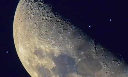 The International Space Station seen in a time-lapse photograph travelling across the face of the moon.