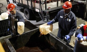 Workers in San Francisco dump bottles of used cooking oil into a dumpster as part of the SFGreasecycle program, which collects used cooking oil from restaurants to be recycled into biofuels. According to a recent report by San Francisco nonprofit group Next 10, California continues to be the nation's leader in venture capital funding for green technology, resulting in reduced greenhouse gas emissions.