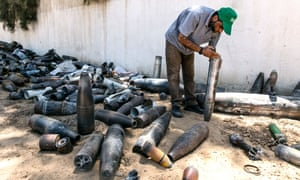 A bomb disposal official collects unexploded ordnance in and around Gaza city.