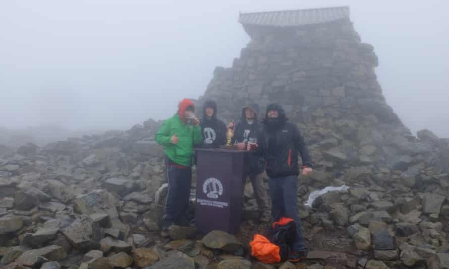 The students and Box Steam brewery barman enjoy a crafty pint at the 1,344-metre summit of Ben Nevis.