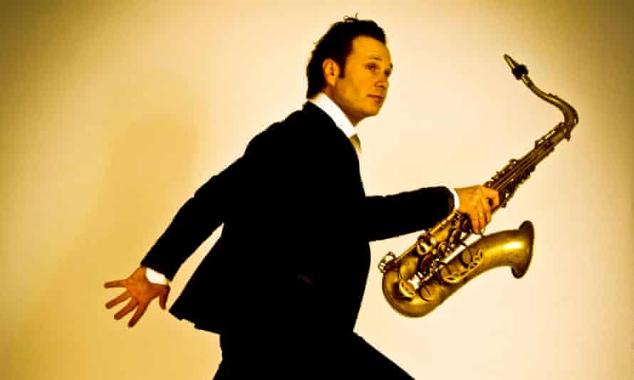 mulo francel holding a tenor sax in one hand in a walking pose
