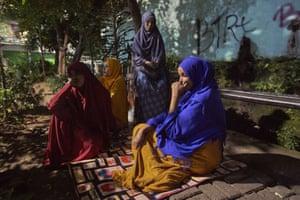 Homeless Somalian refugee women sit in the street at night in Jakarta.