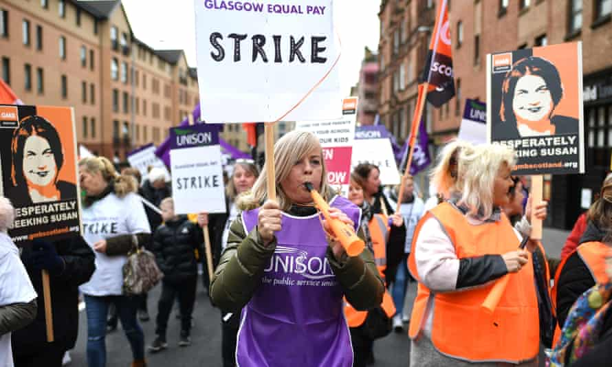 Demonstrators hold placards as they march for equal pay for Glasgow council workers.