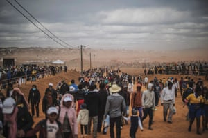 The faithful brave an early morning dust storm as they gather for a holy mass held by Pope Francis in Antananarivo.