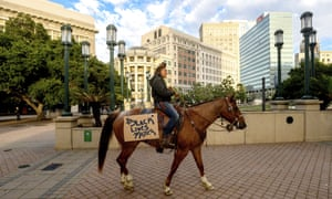 Brianna Noble rides Dapper Dan through downtown Oakland on Friday.