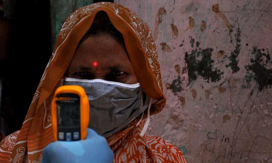 A woman has her temperature taken during mass  screening in Mumbai